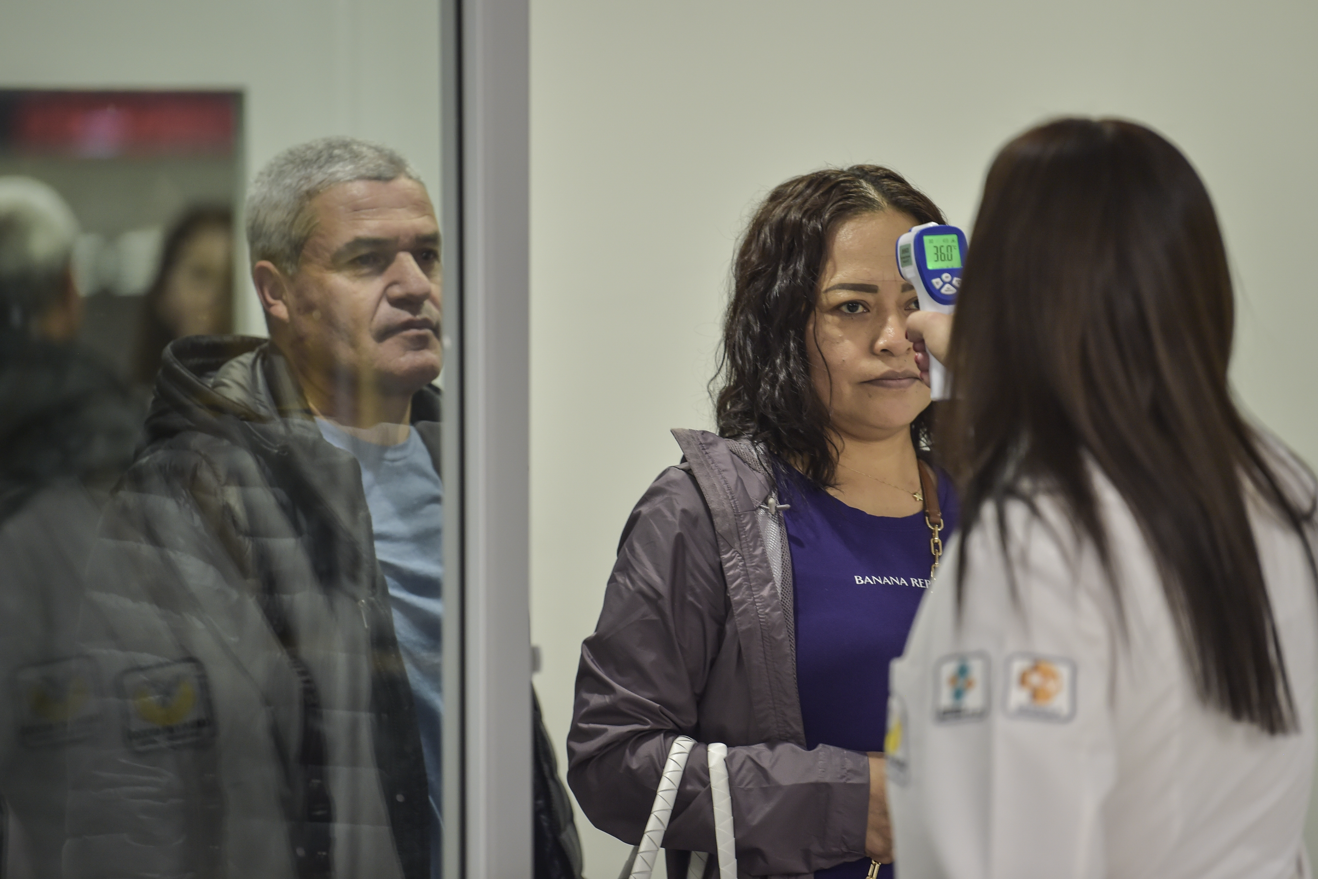 El personal de salud internacional verifica la temperatura de un pasajero como medida preventiva frente a la pandemia mundial de coronavirus COVID-19, en el aeropuerto internacional Benito Juárez en la Ciudad de México, el 13 de marzo de 2020.