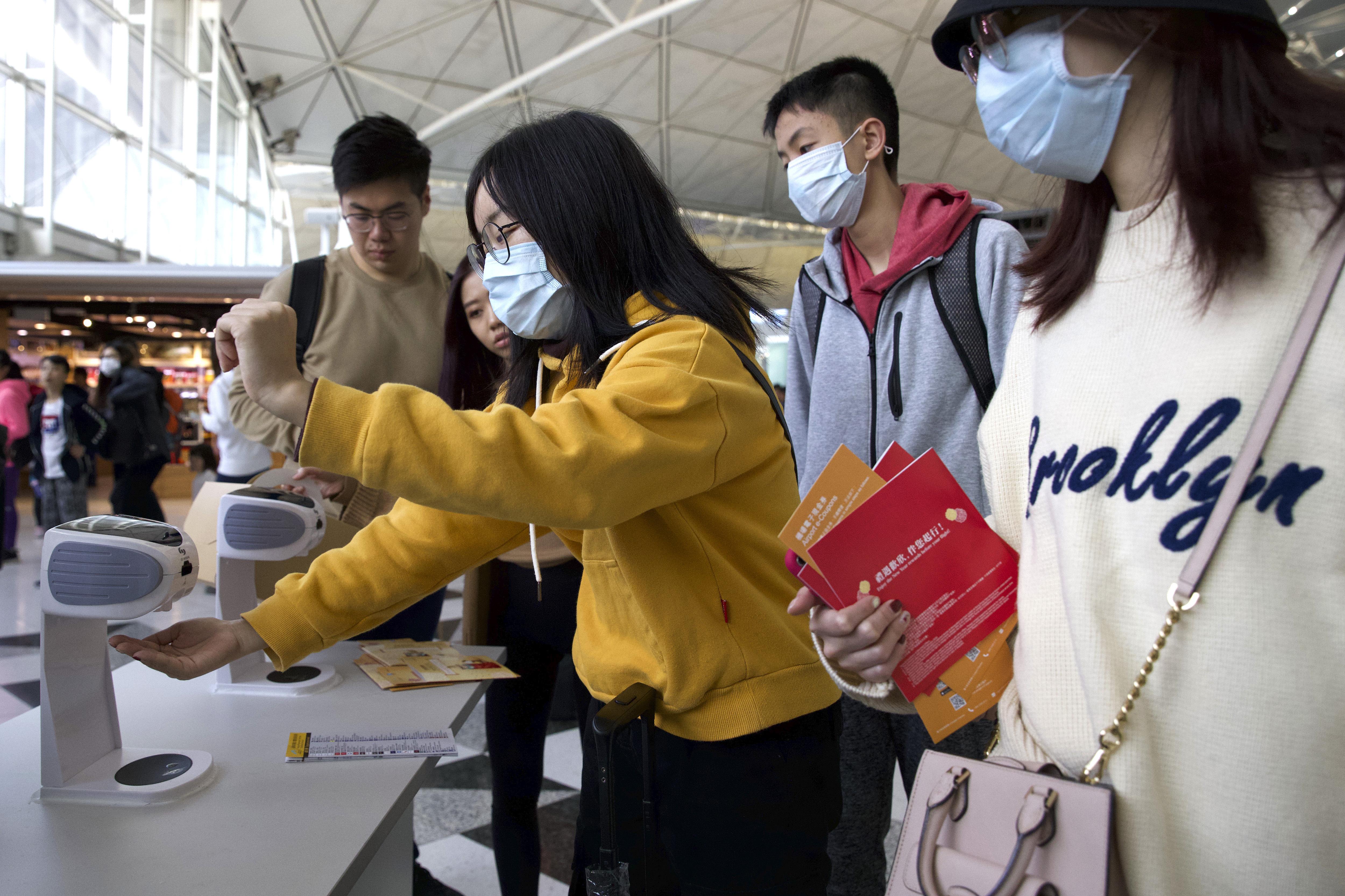 Viajeros con máscaras faciales se reúnen en el aeropuerto internacional de Hong Kong en Hong Kong, el martes 21 de enero de 2020. (Foto AP / Ng Han Guan)