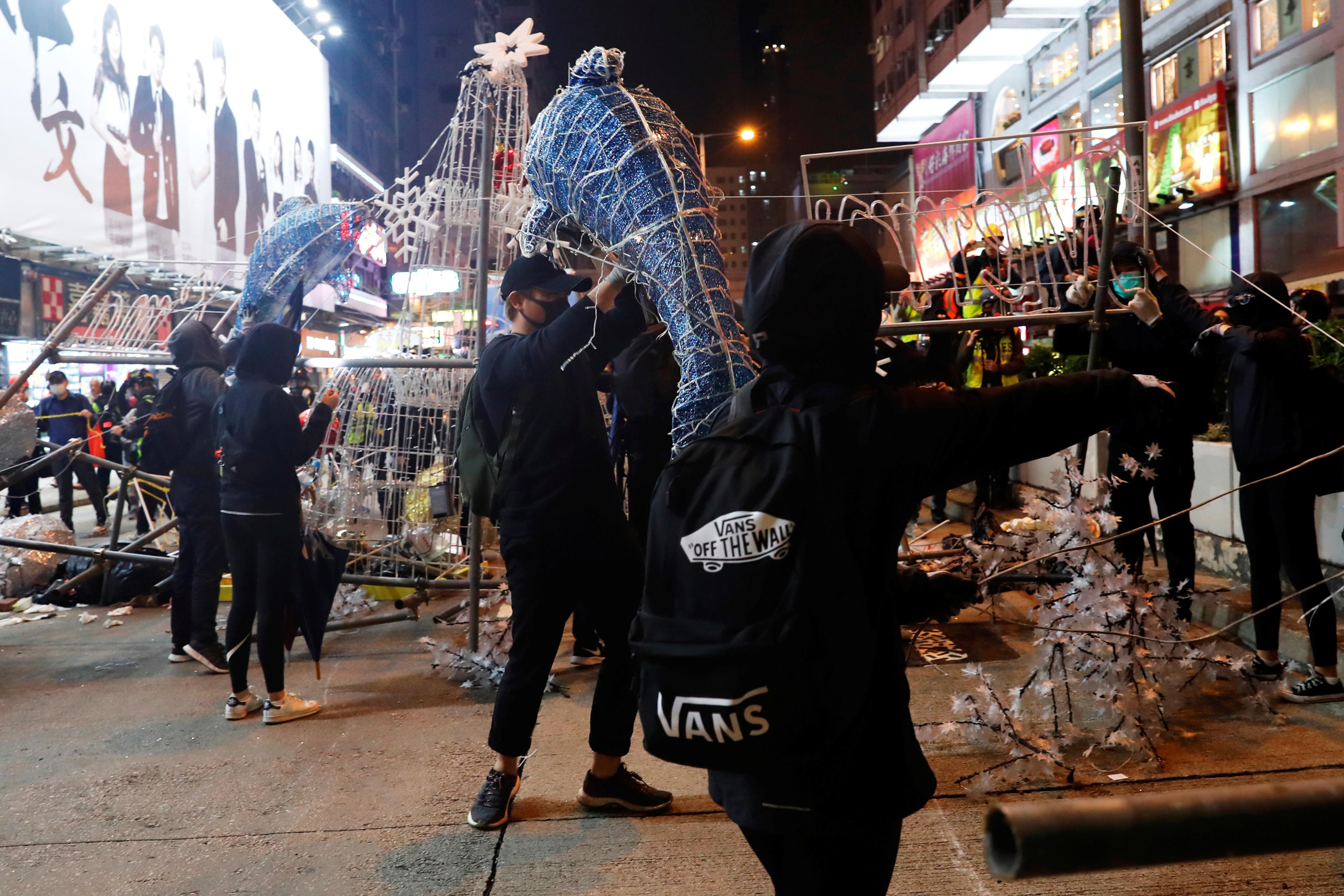 Manifestantes contra el gobierno desarman las decoraciones colocadas en las calles de Hong Kong para celebrar el año nuevo