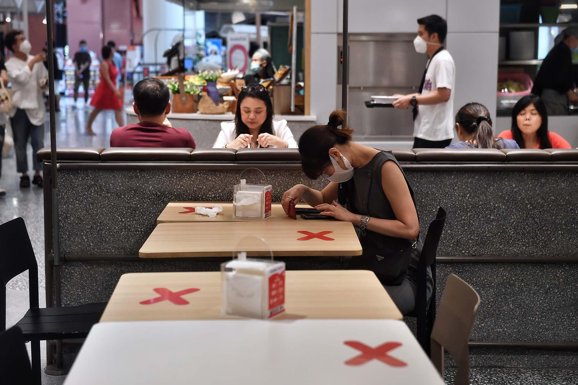 Las cruces señalan los lugares a evitar para mantener la distancia social en el patio de comidas de un centro comercial en Bangkok.