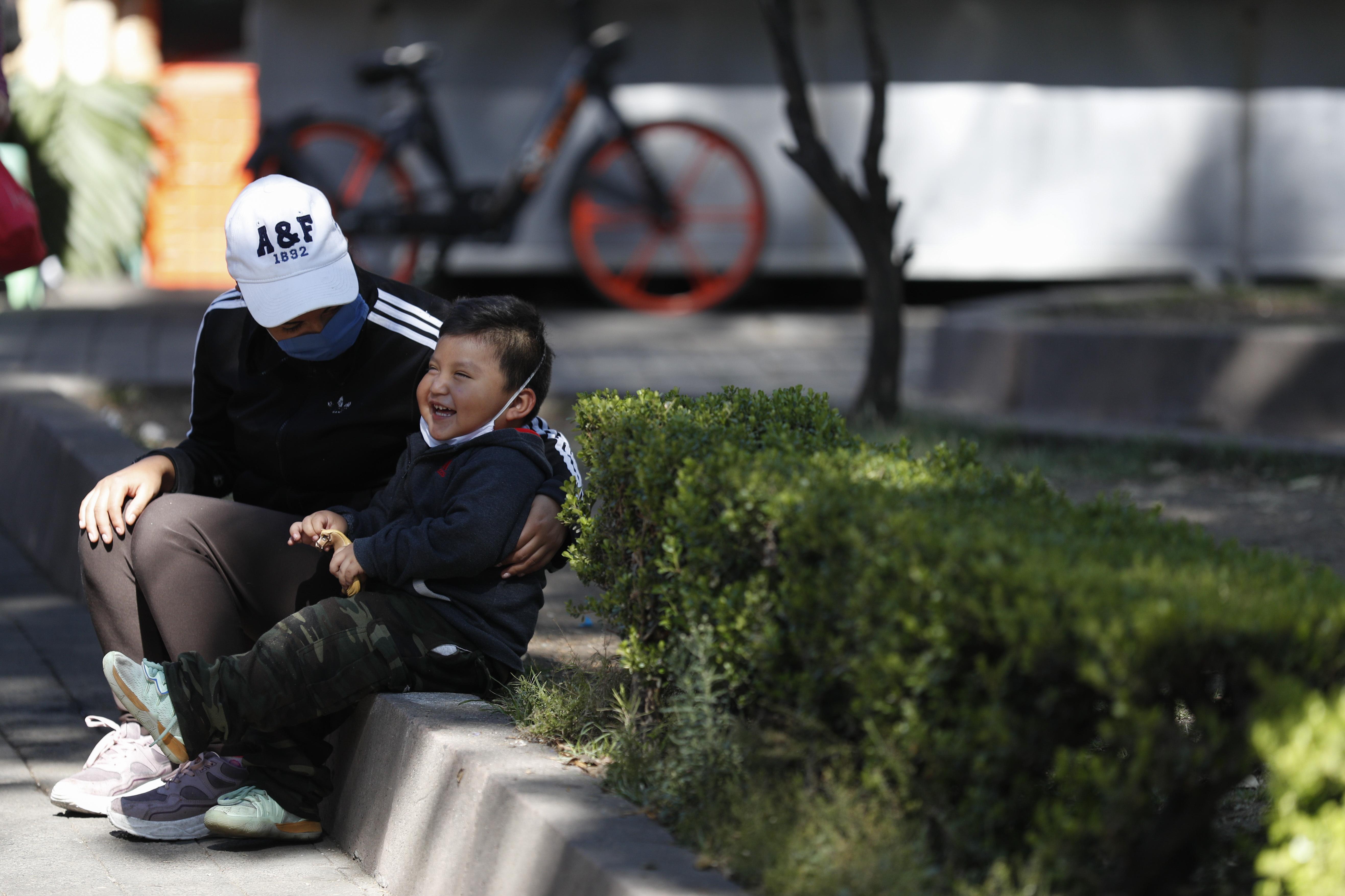 Una mujer, con una máscara facial protectora, y su hijo se sientan en una acera en la Ciudad de México, el miércoles 25 de marzo de 2020.