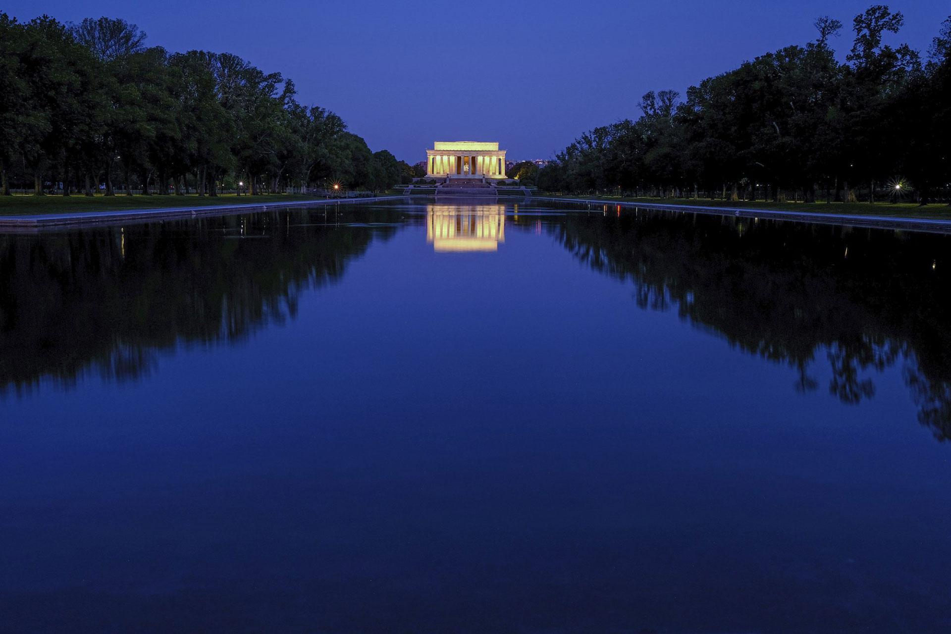 El Lincoln Memorial se refleja en las tranquilas aguas de la piscina reflectante en el National Mall en Washington, EEUU, antes del amanecer del miércoles 29 de abril de 2020. (Foto AP / J. David Ake)