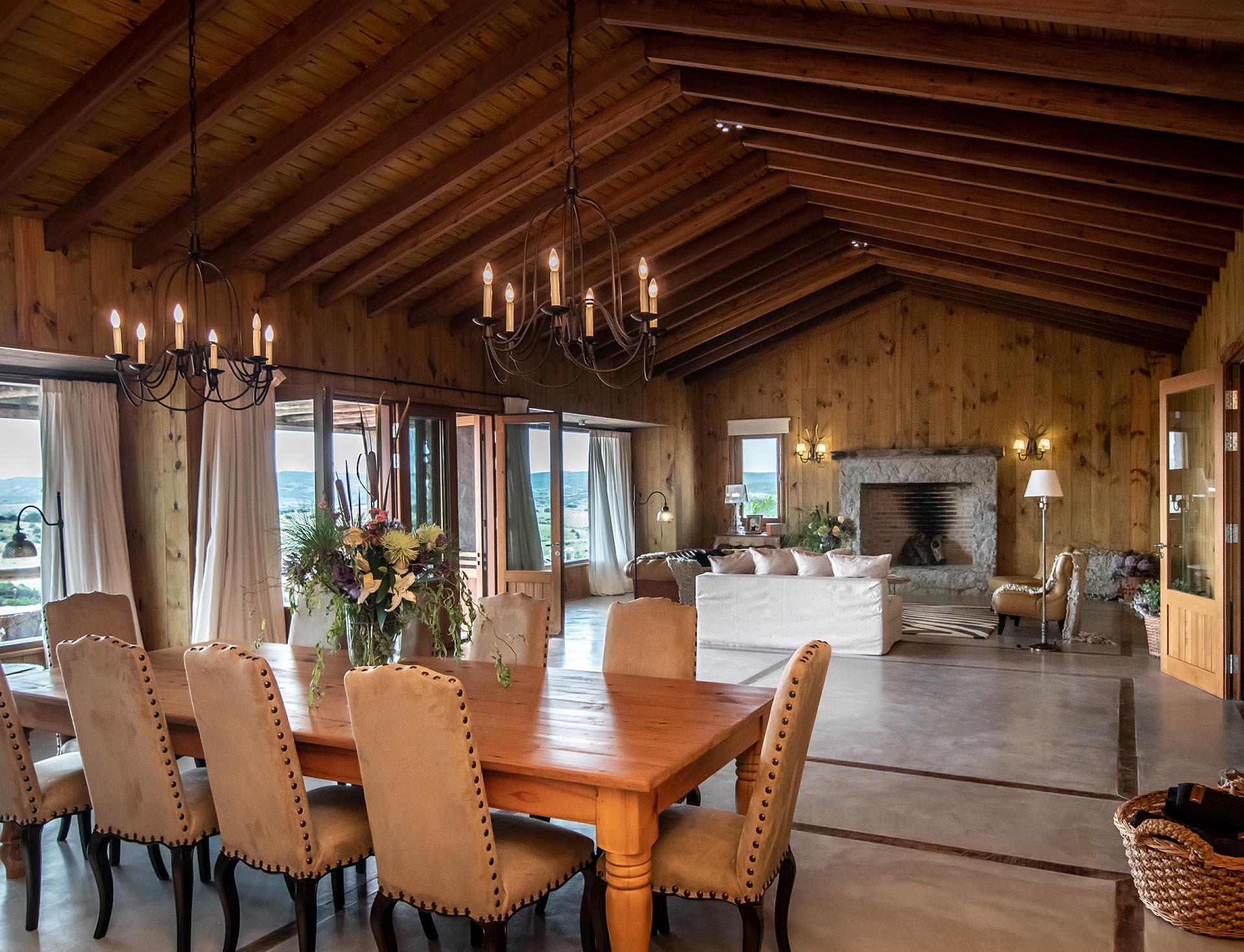 La casa cuenta con una gran sala de estar con maderas recuperadas, y una chimenea rodeada de piedra y grandes ventanales