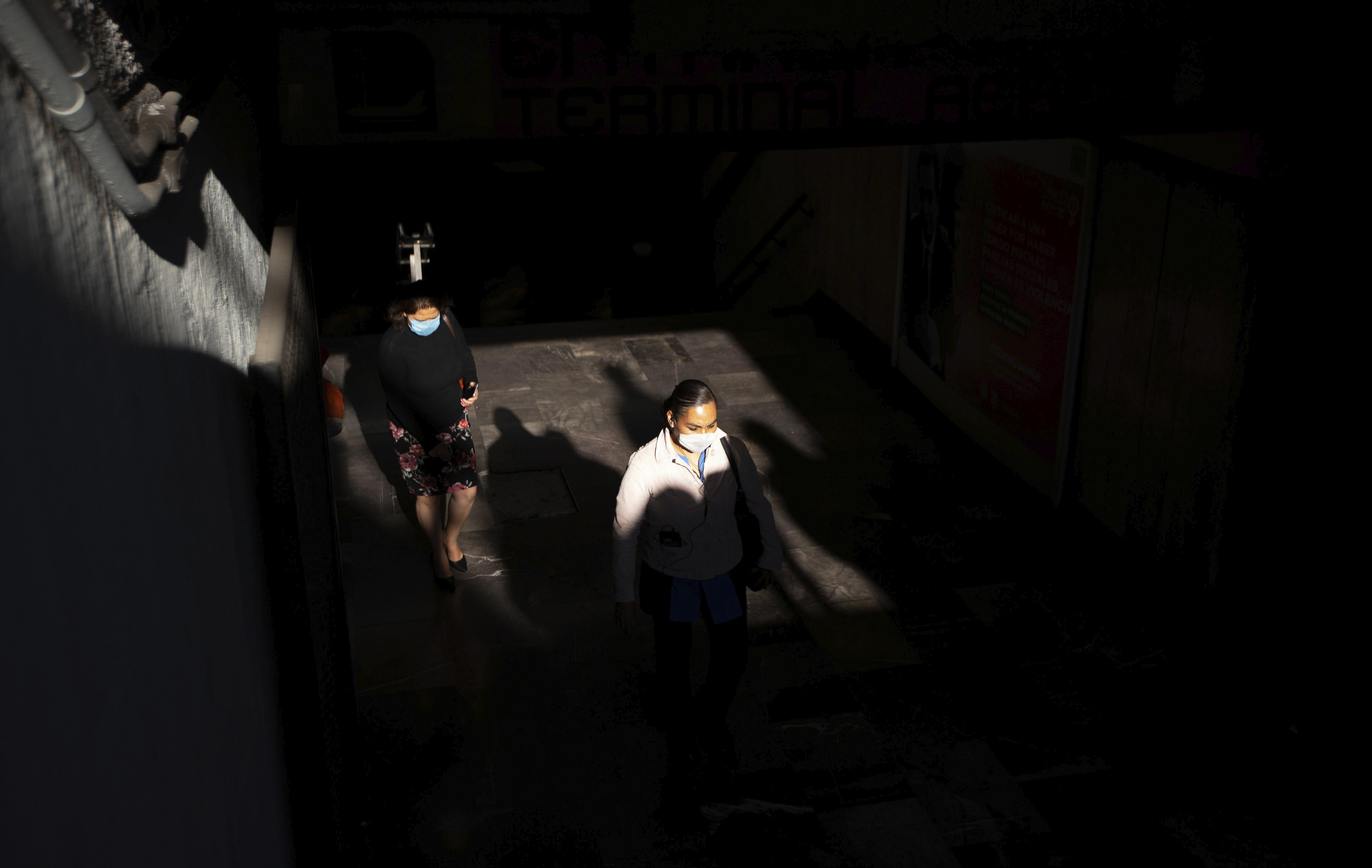 Algunos peatones usan máscaras faciales protectoras salen de una estación de metro en la Ciudad de México, el miércoles 25 de marzo de 2020.