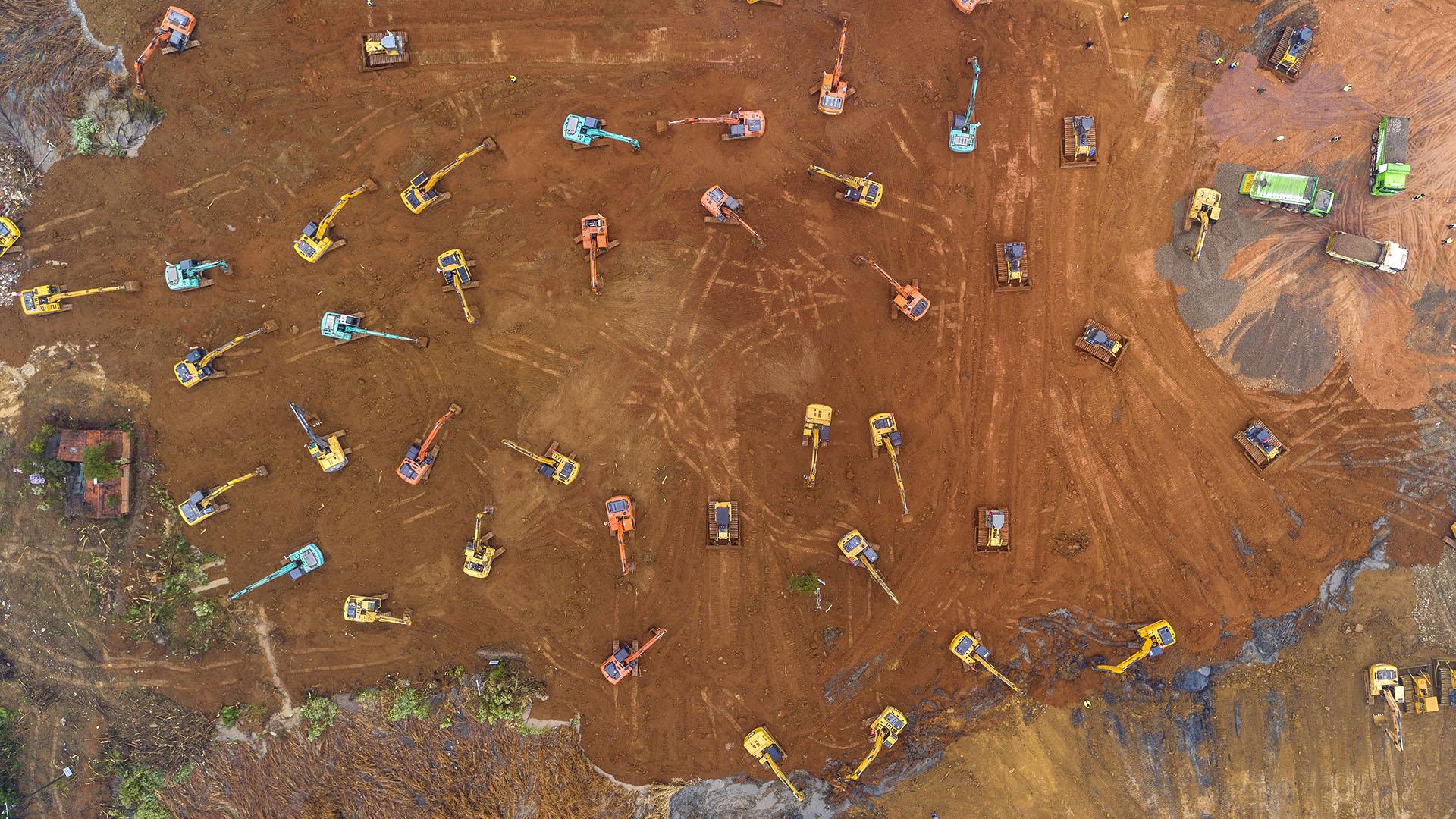 En Wuhan trabajan más de 50 máquinas sobre el terreno en el que se planea levantar un hospital en 10 días (Photo by STR / AFP)