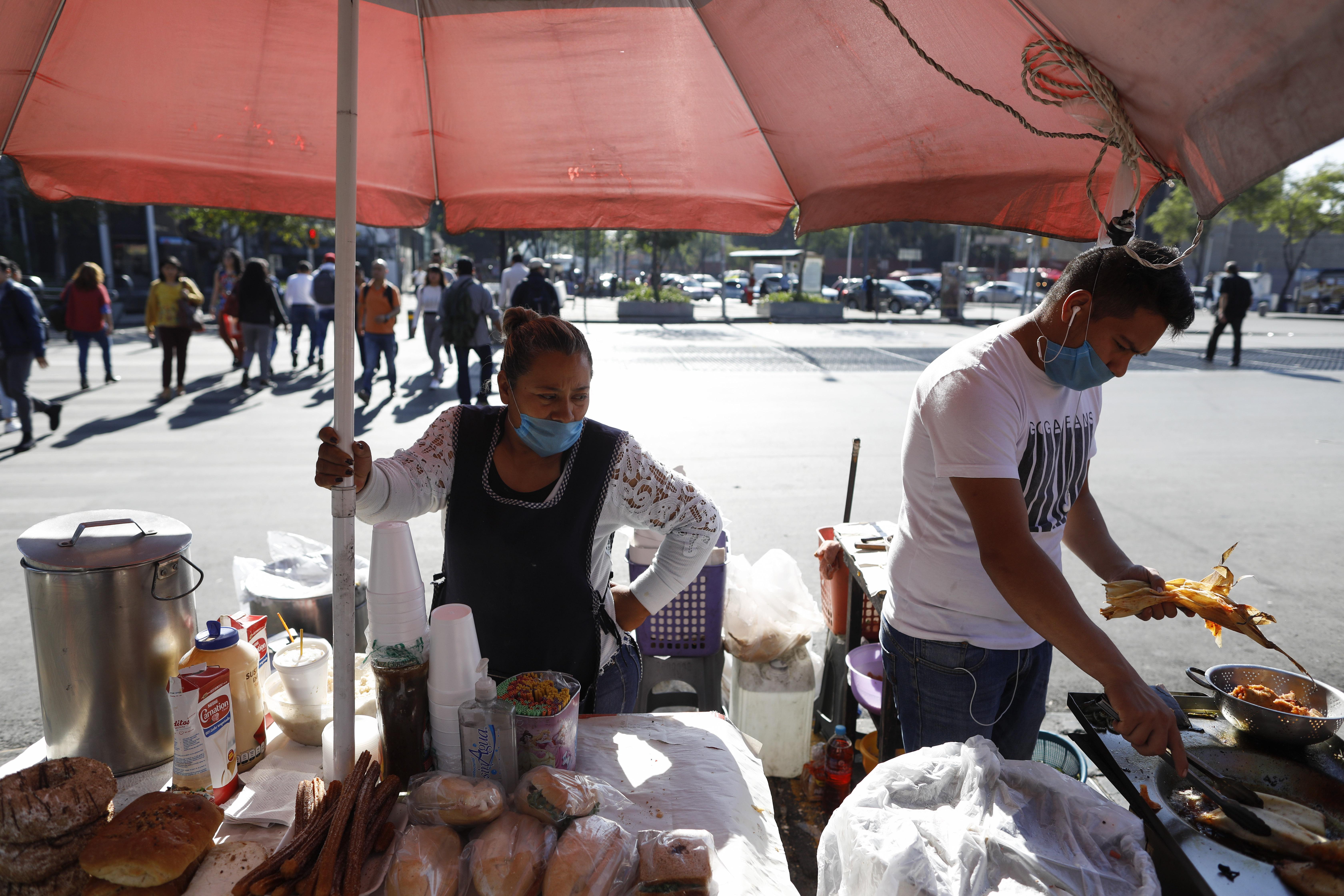 """Lourdes Sanvicente, de 45 años, a la izquierda, y un compañero de trabajo usan máscaras protectoras mientras venden tamales, sándwiches y pasteles en un puesto callejero en la Ciudad de México, el miércoles 25 de marzo de 2020. Sanvicente, quien duda La existencia del nuevo coronavirus, dice que tanto ella como su esposo trabajan como vendedores ambulantes de alimentos, y juntos ganan 320 pesos (alrededor de $ 13.50) por día para mantenerse a sí mismos y a sus cinco hijos. """"No hay otra opción"""", dice, """"tengo que mantener a mis hijos""""."""