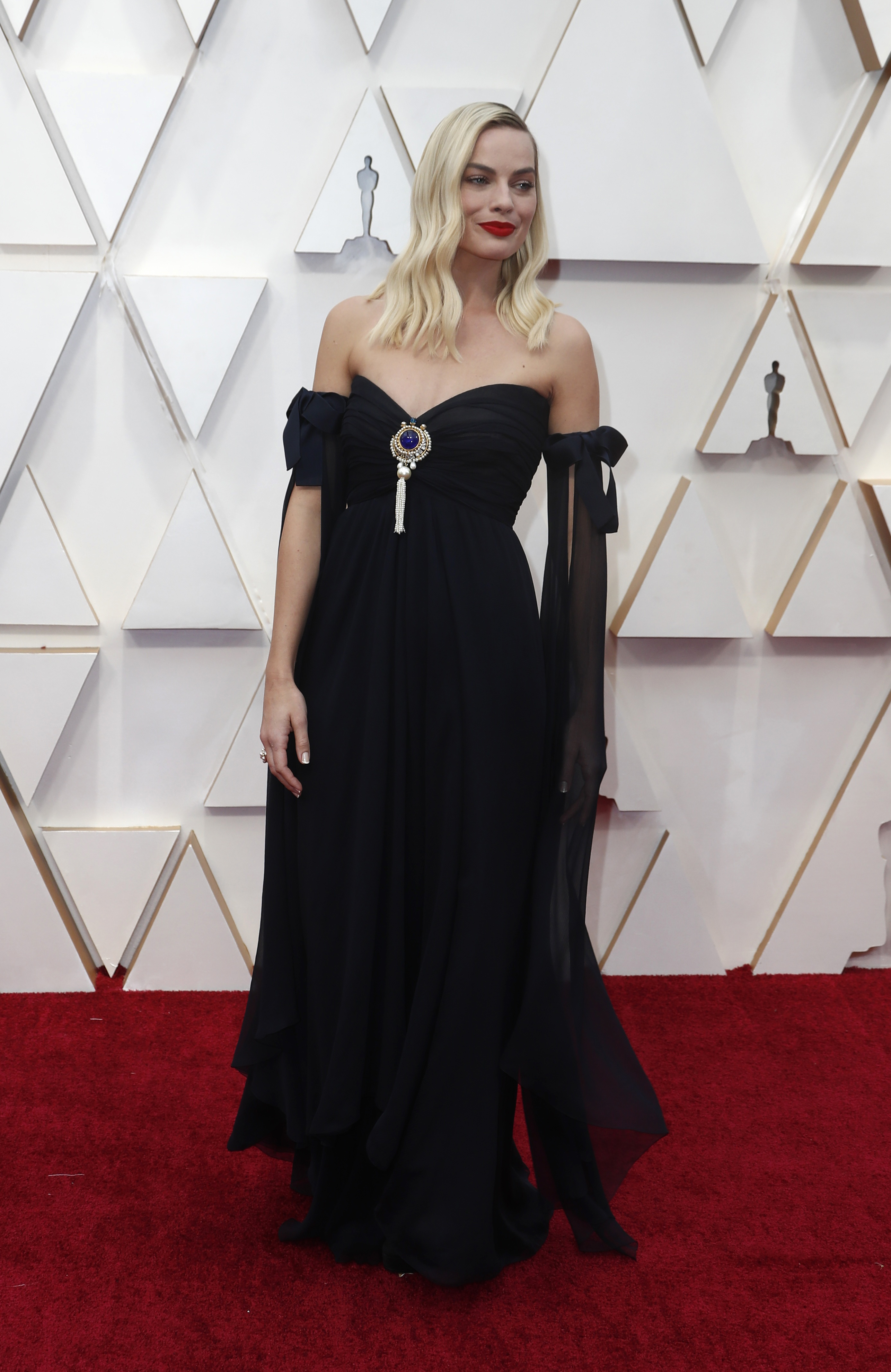 Margot Robbie, optó por un diseño de seda en negro con un aplique con gemas de colores en el escote corazón. El diseño del vestido también tuvo detalles de moños en las mangas. El beauty look de la actriz fue cabello suelto y resaltar su maquillaje con labios rojos