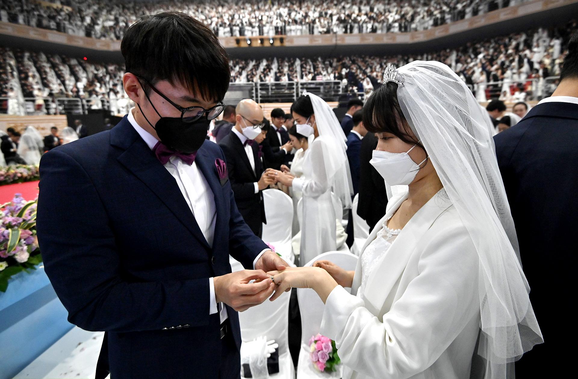 Las parejas con máscaras protectoras asisten a una ceremonia de boda masiva organizada por la Iglesia de Unificación en el Centro Mundial de la Paz de Cheongshim en Gapyeong el 7 de febrero de 2020 (Jung Yeon-je / AFP)