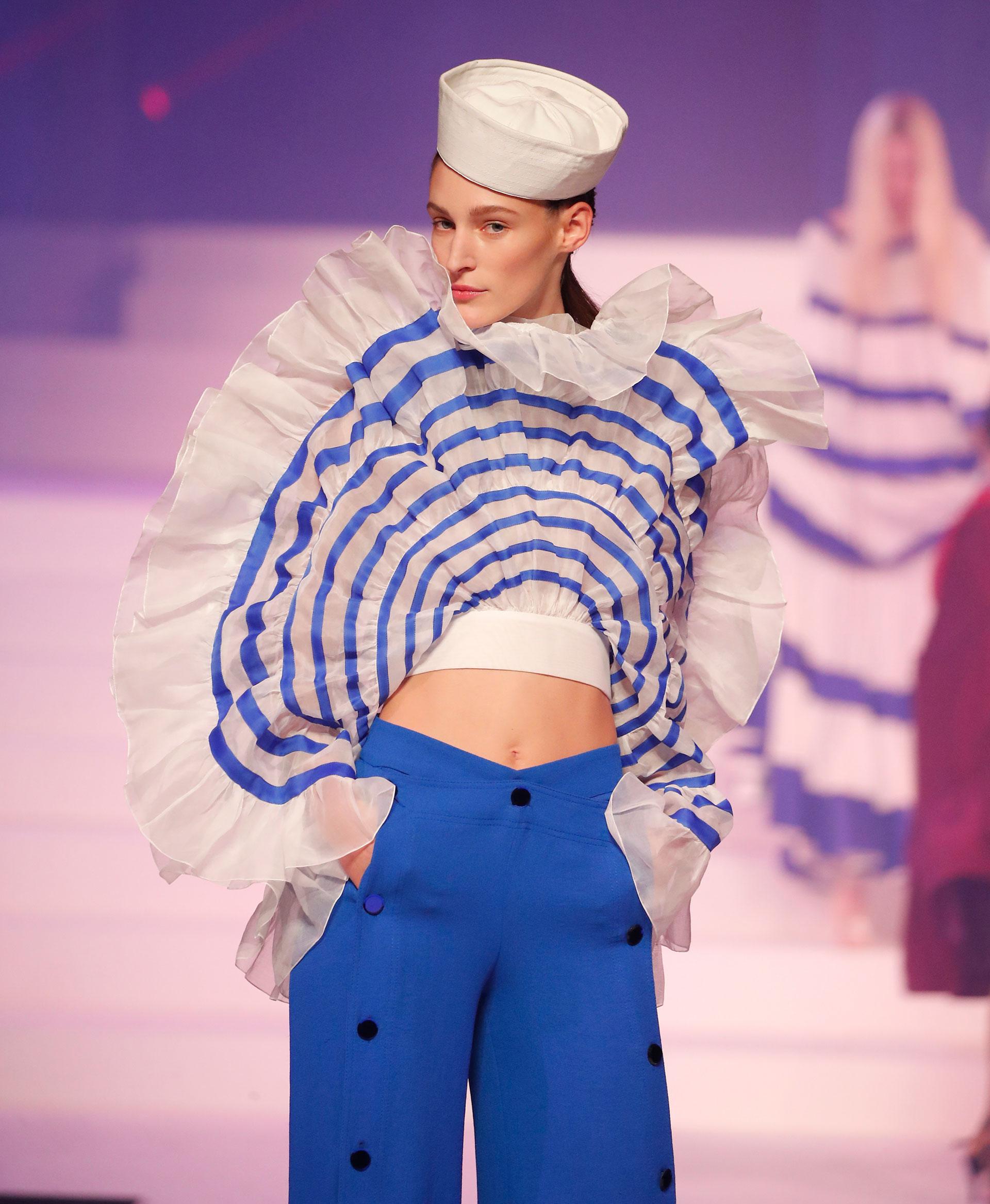 Otro diseño al estilo navy que presentó Jean Paul Gaultier en el último desfile en París. Con el tradicional gorro marinero, un pantalón azul tiro alto con botones grandes y blusa rayada blanca y azul