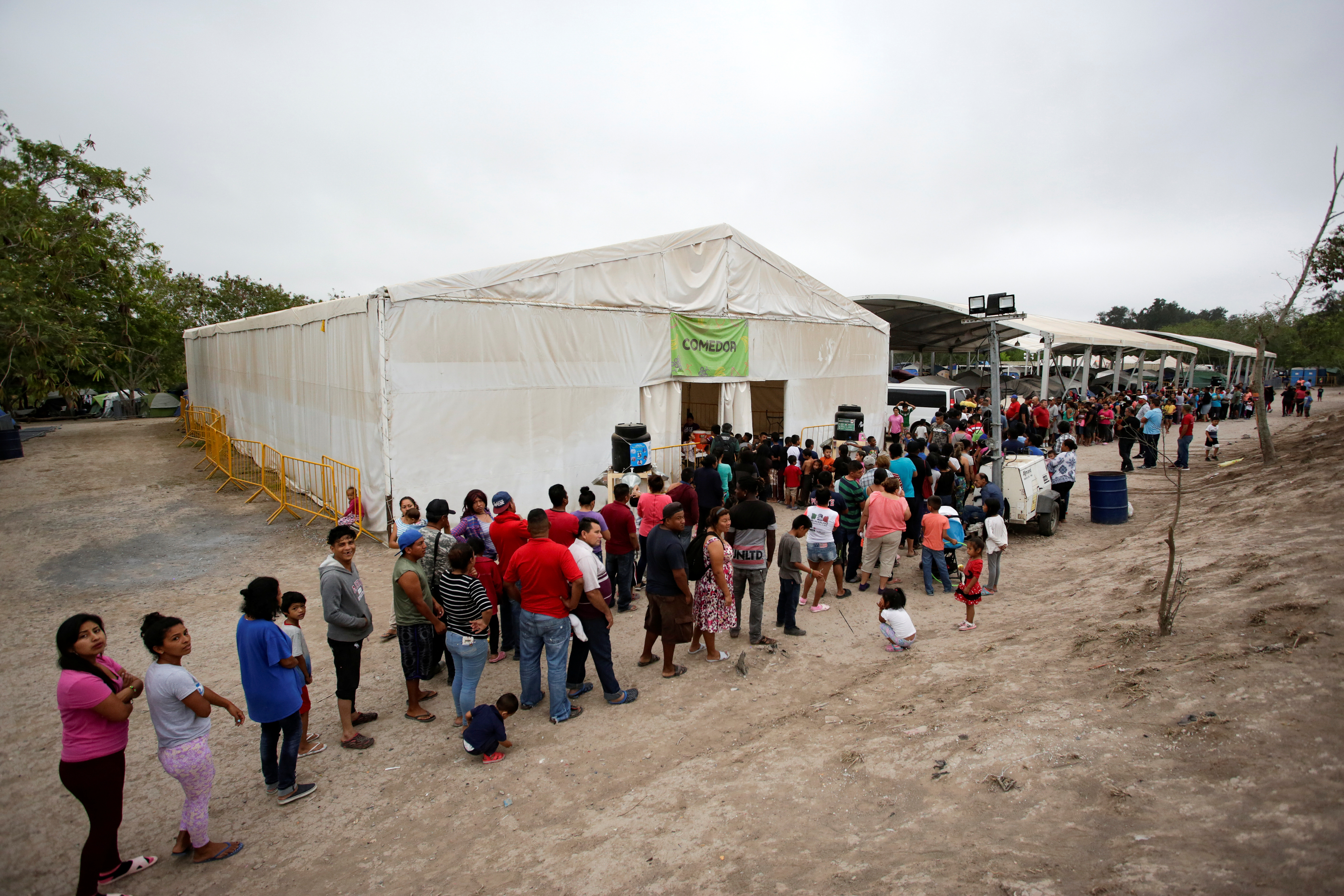 Los migrantes que buscan asilo en los EE. UU. Hacen cola para obtener alimentos en un campamento de más de 2,000 migrantes, mientras las autoridades locales se preparan para responder al brote de la enfermedad por coronavirus (COVID-19), en Matamoros, México, 20 de marzo de 2020.