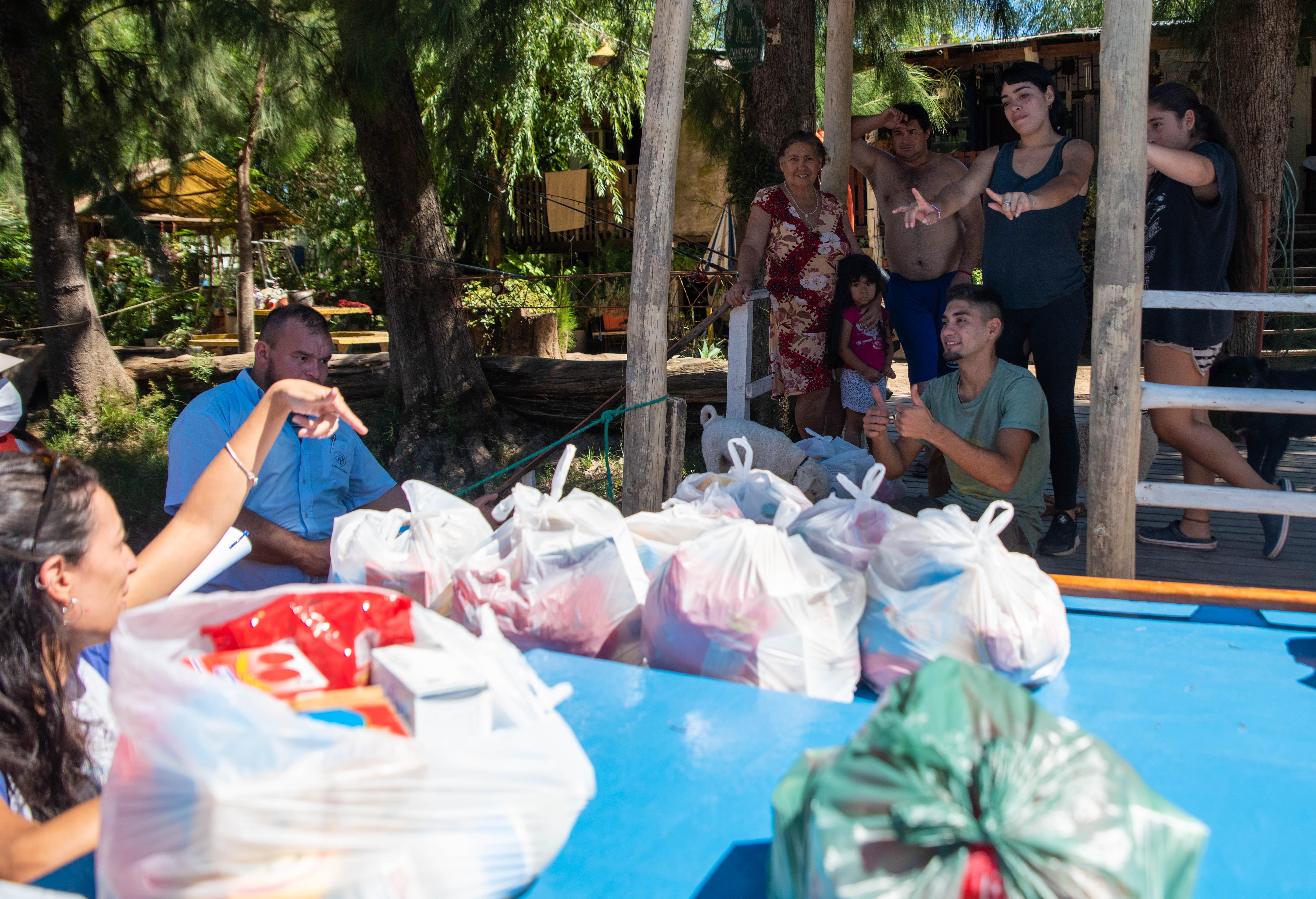 Los docentes se despiden de la familia de uno de sus alumnos después de entregarle los kits alimenticios. (Foto: Franco Fafasuli)